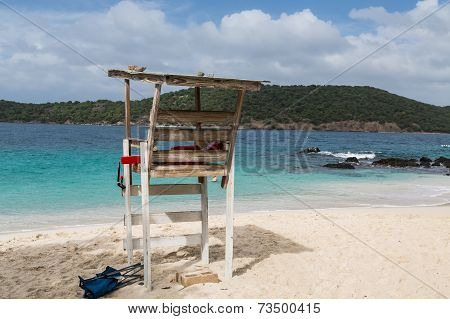 Lifeguard Chair On Beach By Blue Water