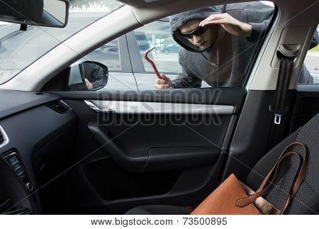 Thief is looking for valuables in a car