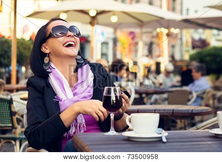 Happy woman sitting in outdoor cafe