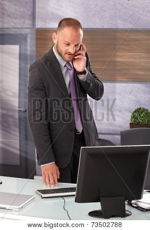 Businessman standing in office, using computer, talking on mobilephone.