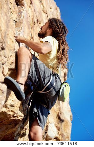 A rockclimber finding a foothold on the steep mountain he's climbing