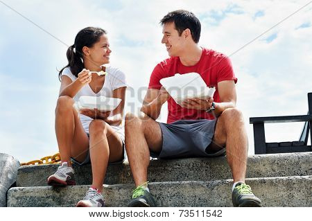 A happy couple sitting together in fitness clothing having their takeaway meals on the docks
