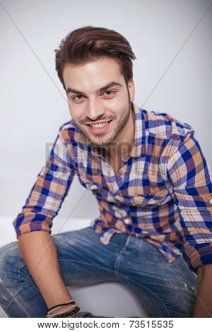 Close up picture of a young fashion man smiling for the camera while relaxing on the floor.