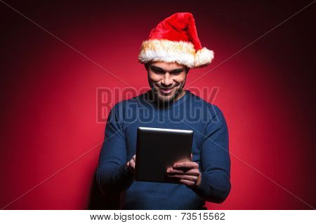 Young santa man smiling while reading on a tablet pad computer. On red background.