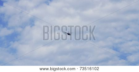 Helicopter Flightning In Blue Sky With Clouds