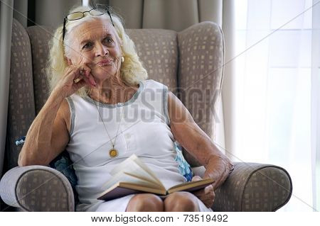 A content elderly woman sitting on her sofa with a book in her lap