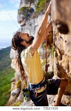 A man with dreadlocks climbing up a steep mountain with a harness and rope and looking up