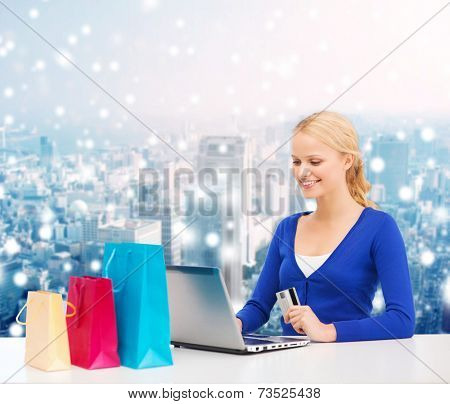 christmas, holidays, technology and shopping concept - smiling woman with shopping bags, credit card and laptop computer over snowy city background