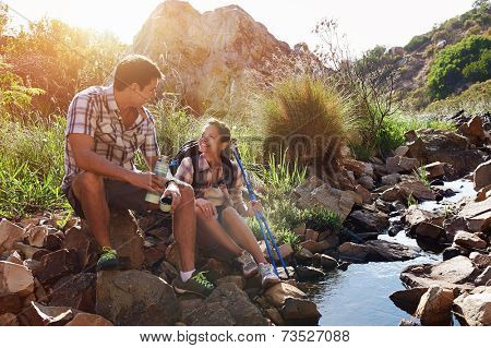 A happy hiking couple sitting by a dam in a nature reserve