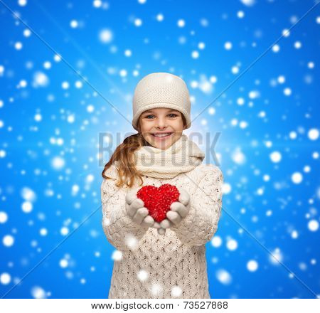christmas, holidays, childhood, presents and people concept - dreaming girl in winter clothes with red heart over blue snowing background