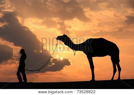 Silhouetted Person With A Camel At Sunset, Thar Desert Near Jaisalmer, India