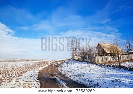 Idyllic winter scene with house and snow covered fields
