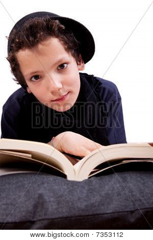 Boy Lying On A Pillow Reading
