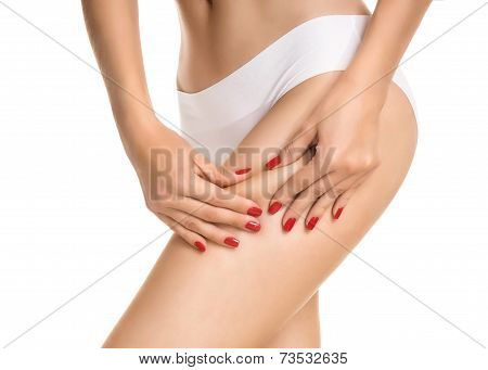 Female squeezing buttock and showing no cellulite in her perfectly shaped body. Isolated on white.