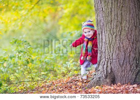 Sweet Funny Baby Girl In A Red Coat And Colorful Hat And Knitted Scarf Hiding Behind A Big Old Tree
