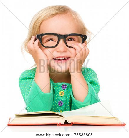 Little girl is reading her book while wearing glasses, isolated over white