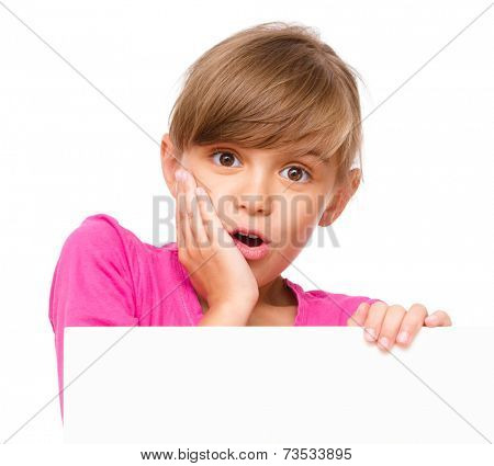 Little girl is looking out from the blank banner, holding her face in astonishment, isolated over white