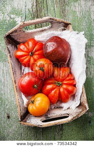 Ripe Fresh Colorful Tomatoes In Wooden Box On Green Wooden Background