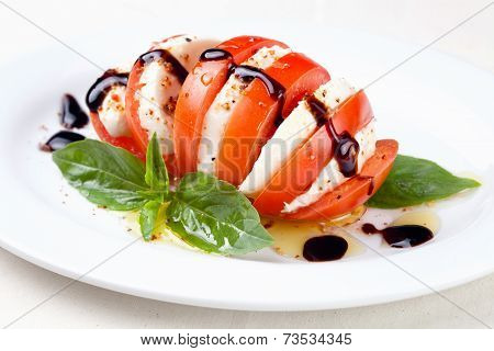 Caprese Salad Tomato And Mozzarella Slices With Basil Leaves On White Background