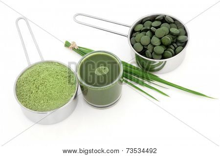 Wheat grass and powder with chlorella tablets and spirulina drink over white background.