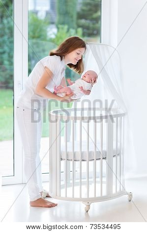 Young Mother Putting Her Newborn Baby To Sleep In A White Round Crib With Canopy