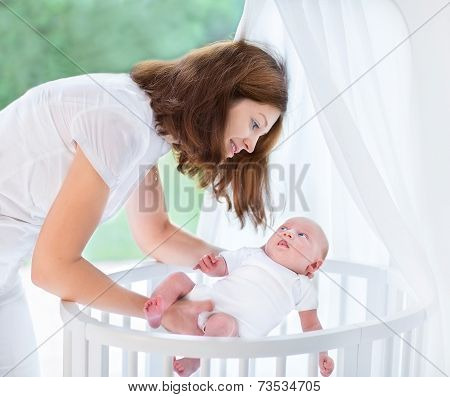 Young Beautiful Mother Putting Her Newborn Baby Into A White Round Crib Next To A Window