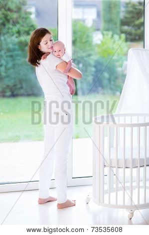 Young mother putting her newborn baby to sleep in a white bed with canopy next to a big window