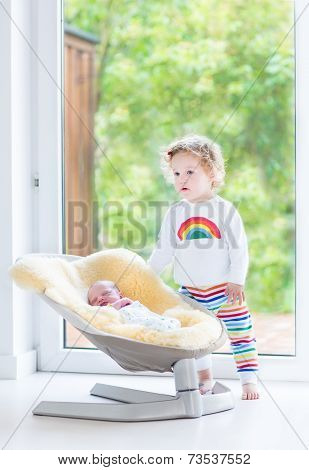 Cute Toddler Girl Playing With Her Newborn Baby Brother Relaxing In A Swing Next To A Big Window