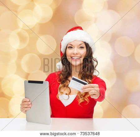 christmas, technology, shopping and people concept - smiling woman in santa helper hat with tablet pc computer and credit card over beige lights background