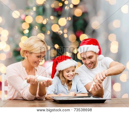food, family, happiness and people concept - smiling family in santa helper hats with glaze and pan cooking over christmas tree lights background