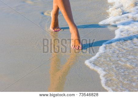 Female leg walking on the beach in the ocean - Narrow depth of field