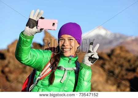Woman hiker taking selfie photo using smartphone while hiking in winter jacket and clothing enjoying outdoor activity. Woman hiker taking self-portrait picture with smart phone camera.
