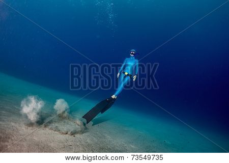 Free diver ascending from the sandy bottom