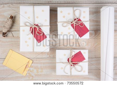 High angle shot of Christmas presents wrapped in white paper and tied with white string. Red gift tags and stars adorn the packages on a white wood table.