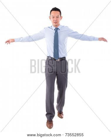 Asian business man walking balance, front view full length isolated over white background.