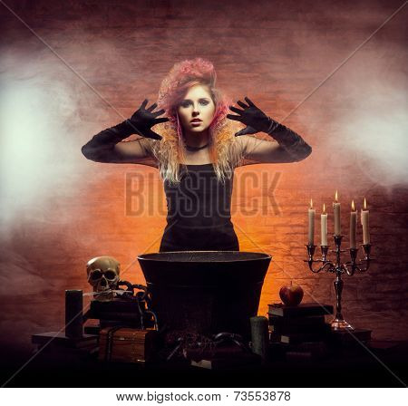 Young and beautiful witch making a witchcraft in dungeon. Halloween concept.