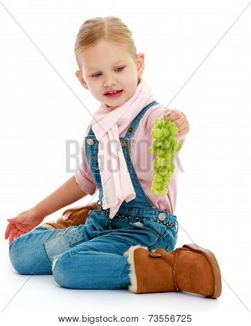 Little girl holding a bunch of grapes.