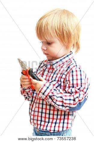 Little boy examines pliers.