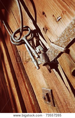 old antique keys and rings against old wooden barn wall, nostalgia