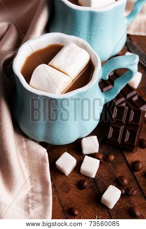 Cups of coffee with marshmallow and chocolate on wooden table
