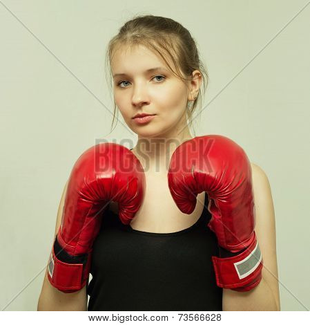 Strong young beautiful girl in boxing gloves