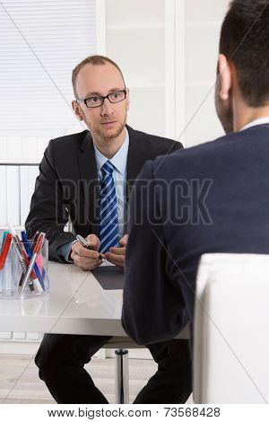 Two business men sitting in the office: meeting or job interview.