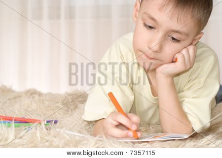 Young Kid With Pencils On The Carpet