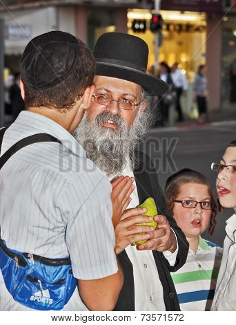 BENE - BERAK, ISRAEL - SEPTEMBER 17, 2013:  The elderly man with gray-haired beard chooses a citrus.  Big market on the eve of Sukkot