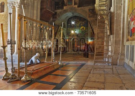 JERUSALEM, ISRAEL - MARCH 9, 2012: The Pilgrim in white scarf prays the Stone of Unction under the lights in the Holy Sepulchre