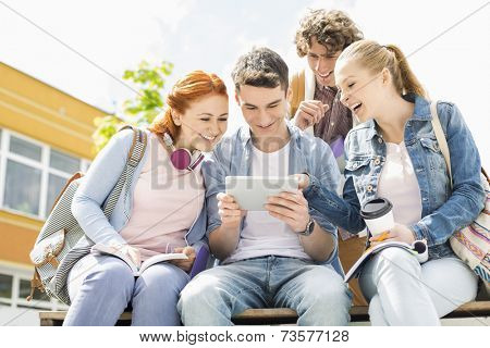 Young students using digital tablet at college campus