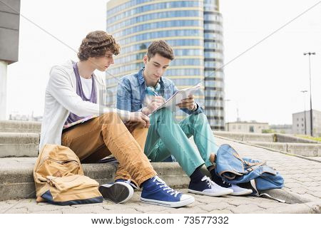 Full length of young male college students studying on steps against building