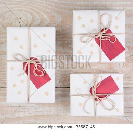 High angle image of Christmas presents wrapped in white paper and tied with white string. Red gift tags and stars adorn the packages on a white wood table. Square format.
