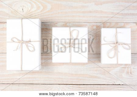 High angle shot of three packages wrapped in plain white paper and tied with white string. Horizontal format on a whitewashed wood table.