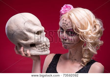 Portrait of young blond girl with Calaveras makeup and a rose fl